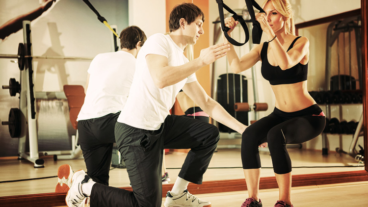 woman-doing-workout-with-fitness-straps-under-supervision-an-personal-trainer